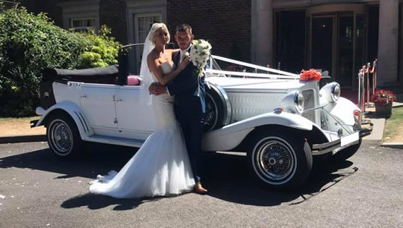 Bride and groom stand in front of Beauford outside of wedding venue