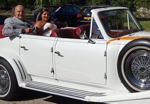 Bride and groom sit in wedding car with roof down