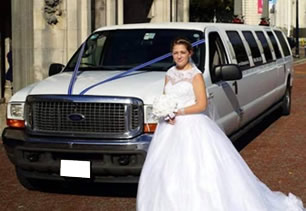 Bride stands with white wedding limousine in front of Cardiff City Hall